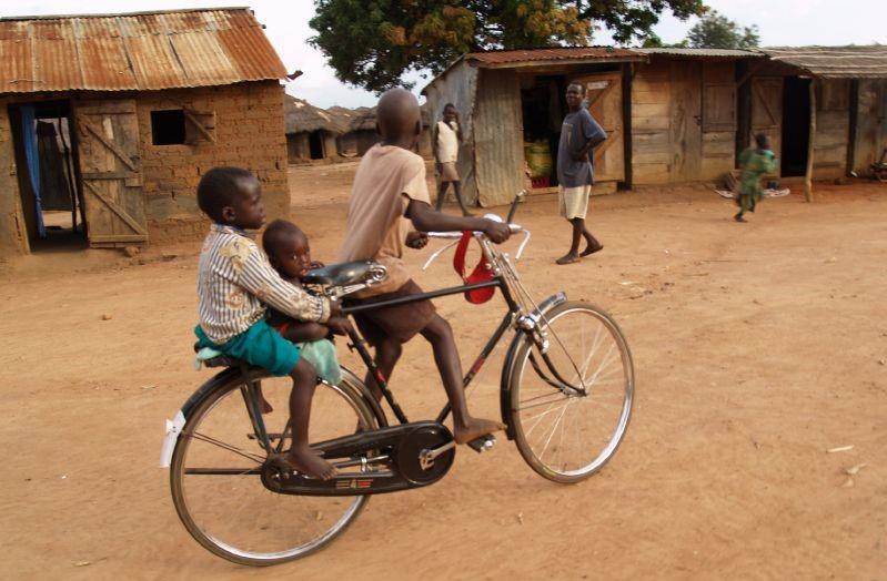 Children riding a bike in Uganda. Photo by Robin Yamaguchi.